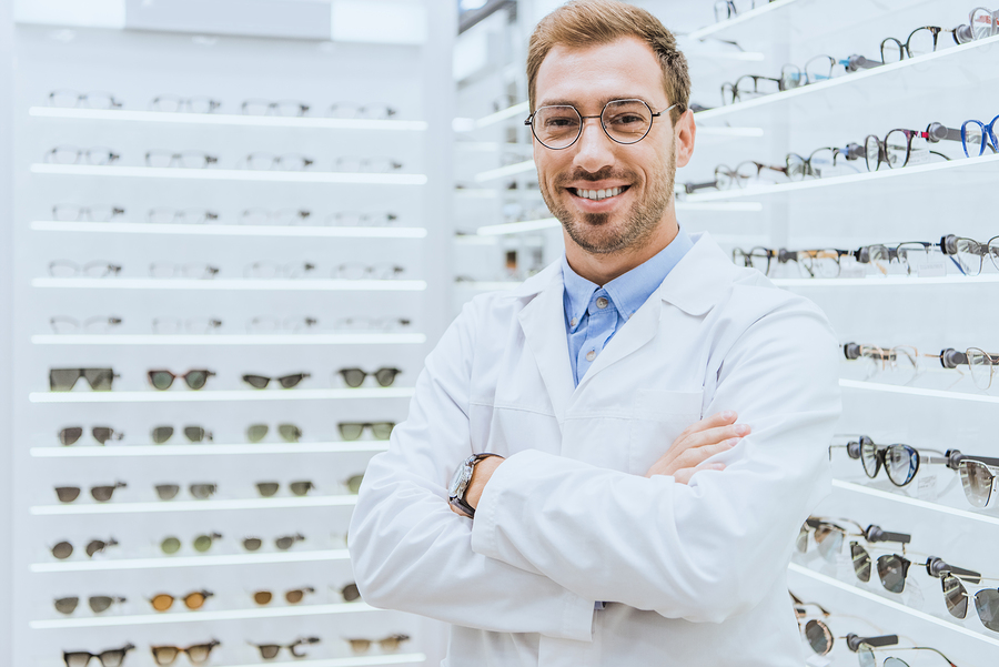 portrait of smiling professional optometrist in glasses posing with crossed arms in optical